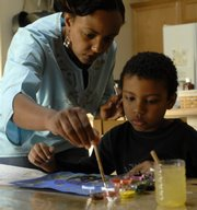 Joachim Case, 7, and his mother, Nini Negash Case, paint at their home. The Cases home school using curriculum from the Lawrence Virtual School.