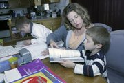 April Hite helps her son Elijah, 5, on an English assignment as his brother Isaiah, 7, works on another assignment.