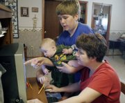 Donna Thomasson enters a grade into the Lawrence Virtual School computer system as her son Luke looks on and holds his brother, 5-month-old Chip. The school day usually lasts from 8:30 a.m. to around noon for the Thomassons.