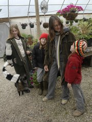 Home schooling for the Davison sisters sometimes means working together as a family in their parents' business, Vinland Valley Nursery. From left in the greenhouse are Emma Davison, 11, Celie Davison, 10, their mother Amy Albright and Bess Davison, 6.