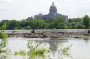 Debris floats past the state Capitol Wednesday in Jefferson City, Mo. The Missouri River is flooding, but at Jefferson City it is not expected to rise anywhere near the record levels set in 1993.