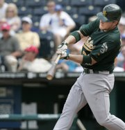 Oakland's Dan Johnson doubles during the sixth inning against Kansas City. Johnson also hit two home runs and went 4-for-4 during the Athletics' 17-3 victory Thursday in Kansas City, Mo.