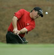 PHIL MICKELSON CHIPS TO THE SEVENTH GREEN during the first round of the Players Championship. Mickelson finished at 5 under Thursday to grab a share of the first-round lead with Rory Sabbatini at the Sawgrass Course in Ponte Vedra, Fla.