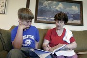 Donna Thomasson teaches her son, Luke, at their home near Wellsville.