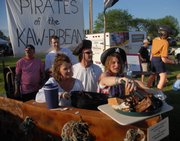 Tricia Clark, left, holds a tray full of ribs as Kara Perry puts them on a plate Friday evening as part of the Sertoma Barbecue Cook-off corporate challenge. Clark and Perry were part of a team from Factory Direct Appliance and Custom Wood Products. The team, which won best booth award, had a pirate theme. The Sertoma State Championship Barbecue Cook-off resumes today at Broken Arrow Park.