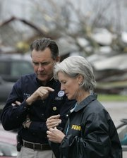 FEMA Director R. David Paulison, left, talks with Kansas Gov. Kathleen Sebelius during a tour of tornado damage Wednesday in Greensburg. Sebelius and other leaders are discussing how to rebuild Greensburg after last week's destruction.