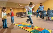 Six-year-old Abigail LePage takes a leap down the hopscotch pad during physical education class as Deavynn Schlesener, 5, and Abigail's brother Josiah LePage wait for their turn at the Community Bible Church, 906 N. 1464 Road. At right is Lana Groundwater, an educator with TEACH, a local Christian home-school group in Lawrence that meets Tuesdays at the church.