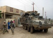 U.S. soldiers on foot and a Stryker armored vehicle move through a neighborhood in Ramadi, Iraq, 70 miles west of Baghdad on April 27. A string of heavy losses from powerful roadside bombs is raising new questions about the vulnerability of the Stryker, the Army's troop-carrying vehicle hailed by supporters as the key to a leaner, more mobile force.