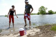 Kristi Wenger and Mitch Langley, both of Lawrence, find the swim beach area and parking lot under water on the west side of Clinton Lake. The lake is at its second highest level in history thanks to the big rains of the last couple of weeks. Wenger and Langley had hoped to swim Monday but settled for sunbathing in the grass near the high water.