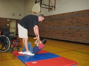 Brad Stoll, an adaptive physical education teacher, helps Kennedy School fifth-grader Taimee Tapedo do sit-ups during a PE class. She did 18 sit-ups in two minutes.