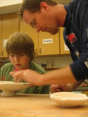 "Jeff Harkin and his son, James, work together on a pottery piece during a May 10 ""Family Pottery"" class at the Lawrence Arts Center."