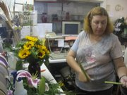 Janis Harvey is surrounded by flowers, ribbons and tools that she uses to make floral arrangements in the back room at Englewood Florist, 1101 Mass.