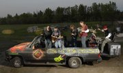 The five-member rock band The Global Warmers has chopped the top off of a 1991 Chevy Suburban that they will perform in Saturday during the Art Tougeau Parade. Inside the vehicle, from left, are Melia Clark, Kelly Howell, Harold Brandt, Joe Osborn and Rick Puhl.