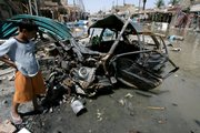 An Iraqi child stands next to the ruins of a car after a deadly blast in the Shiite-dominated neighborhood of Amil in Baghdad. A parked car bomb ripped through a packed outdoor market Tuesday in southwestern Baghdad, killing 25 people and injuring 60 others, despite a 3-month-old security crackdown meant to reduce violence in the capital.