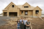 The Astle family, children Kayla, Mason and Ali, and parents Valerie and Evan, pose outside their new 5,700-square-foot home Tuesday in Kaysville, Utah. The state has the biggest concentration of big homes in the nation. Ali, 15, hates the idea of moving from the family's current 2,074-square-foot home. She'll be leaving her friends and attending her arch-rival high school in the fall.