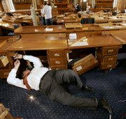 Rep. Bob Bethell, R-Alden, takes apart his desk after the 2007 legislative session adjourned Tuesday in Topeka. House members were allowed to buy their desks and chairs, which will be replaced as the House chamber is renovated before the beginning of the next session.