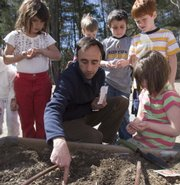 Roger Doiron of Scarborough, Maine, assists students at Pleasant Hill Elementary School in Scarborough with their garden. Doiron started a Web site called Kitchen Gardeners International, which promotes taking control of the food you eat and reducing the distance it travels by growing your own food in your backyard.