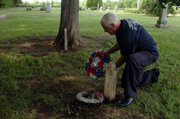 Bob Wandel, a member of Sons of Union Veterans, places a wreath near the tombstone of Anna Jessie, who died at age 5 in 1878, at Clinton Cemetery.