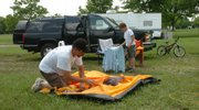 Craig Ritchie and his son Caleb, 7, of Olathe fold their tent Monday morning and prepare to head home after a weekend at Clinton Lake. High water at area lakes closed many boat ramps and some campgrounds.