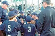 The Clippers' players gather around coach Brett Toalson for instruction Thursday at YSI.