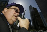 Private security guard Richard Bergendahl talks on his radio in downtown Los Angeles. The 72-story U.S. Bank Tower, formerly known as Library Tower, seen in the background, is the tallest office building on the West Coast and is just down the street from the high rise where Bergendahl works.
