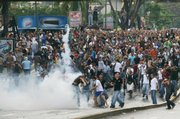 University students throw back tear gas canisters fired by riot police, unseen, in Caracas during protests against Venezuelan President Hugo Chavez's decision to shut down television station Radio Caracas Television. Thousands of people, both opponents and supporters of the move, took to the streets in protest Tuesday.