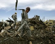 An Army Reserve member removes metal from a pile of debris while helping clean storm damage in Greensburg. Most of the town of 1,400 was destroyed after an F-5 tornado hit the community May 4, 2007, and exposed vulnerabilities in the region's emergency response system.