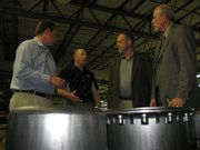 Jim Stinehelfer, CEO of HiPer Technology Inc., second from left, leads a tour of the company&#39;s manufacturing floor at 2920 Haskell Ave., including a stop at a stack of HiPer&#39;s carbon composite wheels. Listening are, from left, Chris Bovis, director of marketing for HiPer; state Rep. Tom Sloan, R-Lawrence; and David Kerr, Kansas secretary of commerce. Below is one of the company&#39;s wheels.