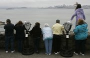 Spectators scan the water at a vista point near Sausalito, Calif., looking south toward San Francisco. Two lost whales last spotted near the Golden Gate Bridge may have slipped back into the Pacific Ocean after a two-week sojourn that took them 90 miles inland up the Sacramento River, scientists said Wednesday.