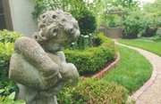 "A statue flanks a pathway that winds through the Fritzel's English-inspired landscape. ""I spend all day in the garden,"" Christine Fritzel says. ""It is a labor of love ... or stupidity."""