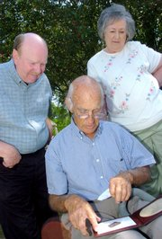 Grafton and Sandra Dodd look over the shoulders of Phil Park in Huntingdon, Tenn., as they look at a dog tag that was found five years ago on Omaha Beach in France. The dog tag belonged to their relative Pvt. William Bernice Clark. The tag was returned to Tennessee on Wednesday, exactly 63 years after D-Day.