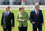 German Chancellor Angela Merkel, center, Russian President Vladimir Putin, left, and U.S. President George W. Bush gather for the group G-8 picture in Heiligendamm, northeastern Germany. The leaders agreed to pursue reductions in emissions that cause global warming, and the chilly relations between Putin and Bush thawed a bit Thursday with discussion about a missile defense system.