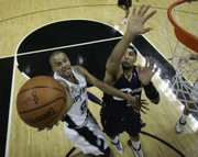 San Antonio Spurs guard Tony Parker (9) shoots over Cleveland Cavaliers forward Drew Gooden, right, in the first half of Game 1. The Spurs won the NBA finals opening game, 85-76, Thursday in San Antonio.