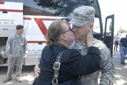Susan Rozell greets her son Tim Rozell, both of Topeka, with a big kiss as he gets off a charter bus. Members of the 130th Field Artillery National Guard out of Topeka arrived from Iraq on Saturday.