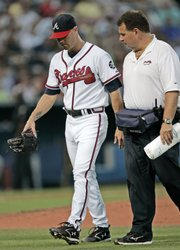 Atlanta Braves starter Tim Hudson walks off the field with a trainer after he was hit on the left leg by a ground ball by Chicago Cubs' Jacque Jones. Hudson had to leave the game, but Atlanta's offense picked up the slack in a 9-5 victory Saturday in Atlanta.