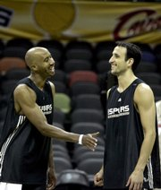 San Antonio forward Bruce Bowen, left, greets teammate Manu Ginobili. The Spurs practiced Saturday in San Antonio and will look to extend their 1-0 series lead in the NBA Finals tonight. Tipoff against the Cleveland Cavaliers is scheduled for 8 p.m.