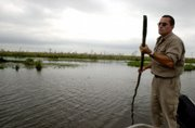 A man pushes his boat in the Esteros del Ibera, north of Argentina, near the area owned by U.S. businessman Douglas Tompkins. Tompkins now owns well more than 1 million acres in Chile and Argentina, a combined area larger than Belgium that he says he wants to save from agribusiness and development.
