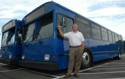 On July 2, 2007, KU on Wheels changed to new buses. Danny Kaiser, assistant director of KU Parking and Transit, with two of the new 40-foot buses, points out the new paint scheme for the buses.
