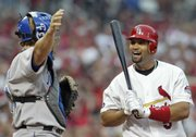 St. Louis' Albert Pujols, right, laughs with Kansas City catcher John Buck as Pujols is intentionally walked. The Royals pitched around Pujols twice, and it paid off both times in Monday's 5-3 victory against the Cardinals in St. Louis.