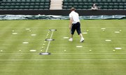 "Technicians prepare the tennis court for calibration of the ""Hawk-Eye"" video line call system. The All England Club will use the system on two of its courts at Wimbledon this year."