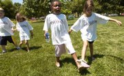 """Ariana Falls, 6, center, yells out """"oww"""" in pain  as her partner, Aliyah Anderson, 6, coaxes her along in a three-legged race in South Park. Youngsters from kindergarten to ninth grade participated in the Lawrence Boys and Girls Club&squot;s annual Juneteenth celebration Tuesday at South Park with games and a barbecue."""