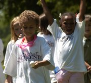 Jason Bennett, 6, left, is cheered on by a teammate as he races with an egg in a spoon in South Park for the Juneteenth celebration Tuesday. Juneteenth marks the day the abolition of slavery was announced in Texas.