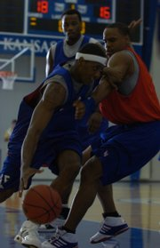 Kansas junior guard Mario Chalmers, left, dribbles around former Jayhawk Michael Lee during a scrimmage at the Bill Self Basketball Camp. Current and ex-Jayhawks scrimmaged Wednesday at Horejsi Center.