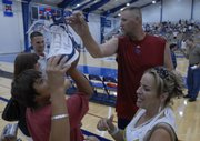 Andrew Hanzel of Lee's Summit, Mo., eyes a size-18 autographed basketball shoe from former Jayhawk and NBA basketball player Greg Ostertag, center, following a scrimmage at the Bill Self basketball camp. At right is Liz Haywood of Greenwood, Mo. Ostertag participated in a scrimmage Wednesday at Horejsi Center.