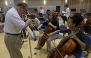 Retired Air Force Col. Arnald Gabriel runs through a part with cellists Nabilah Rawdan, Choctaw, Okla., front right, and Ingrid Freaney, Cedar Rapids, Iowa, before full orchestra rehearsal.