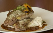 """Citrus peppercorn-crusted pork chops with squash blossoms are featured on this month&squot;s menu at Pachamama&squot;s, 800 N.H. They&squot;re just one example of edible flowers, which can be used as a garnish or as an integral part of a recipe. """"If you can add excitement and indulge more senses for the diner, it will only enhance their food experience,"""" says Sam Siber, operations manager for the restaurant."""