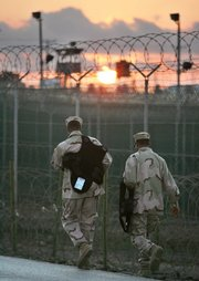 U.S. troopers walk as the sun rises over the razor-wired detention compound at Guantanamo Bay U.S. Naval Base, Cuba, in December 2006. The Bush administration is nearing a decision to close the Guantanamo Bay detainee facility and move its terror suspects to military prisons elsewhere.