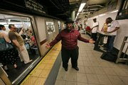 """Michael Lee Anthony sings while accompanied by Alphonso McGruder, right, on keyboards and """"Sugar Ray"""" Sanders, third from right, in performing oldies songs Tuesday as a train prepares to leave the 77th Street subway in New York. City officials say Gotham is about to get a little quieter when new noise regulations take effect July 1."""