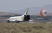 The space shuttle Atlantis lands Friday at Edwards Air Force Base, Calif. Uncooperative weather at Kennedy Space Center forced flight controllers to pass on a landing attempt in Florida.