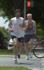 "Lindy Eakin, left, vice provost for administration and finance at Kansas University, runs with members of the ""KU Mad Dog Running Group"" in June in downtown Lawrence. kued2007"